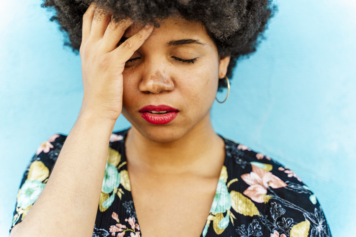 Portrait of Afro-American woman, hand on forehead, blue wall in the background