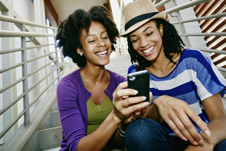 Women using cell phone together on steps