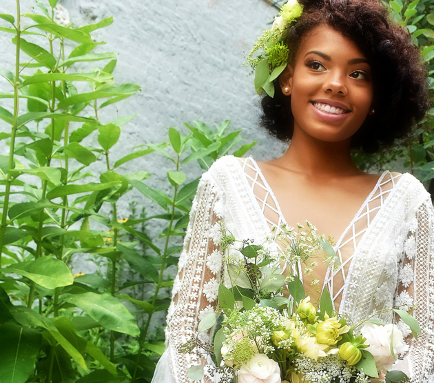 Smiling Young Woman With Bouquet Standing Against Plants