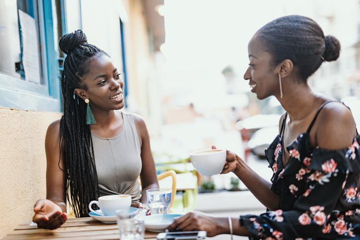 African millennial women drinking coffee outdoors
