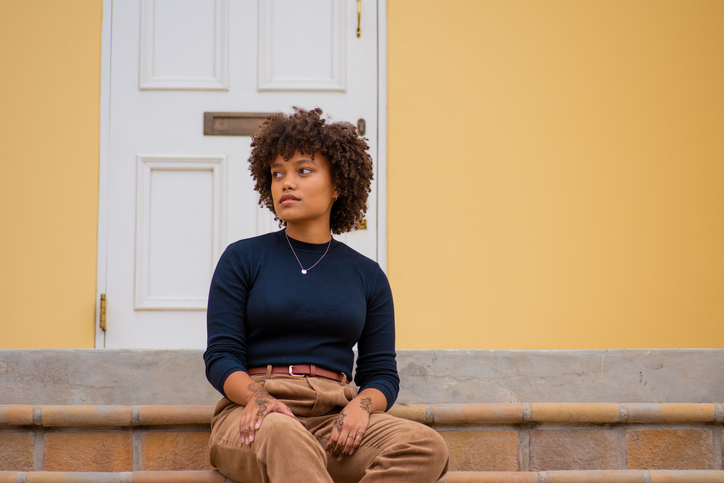 Young Woman Looking Away While Sitting On Staircase Against House