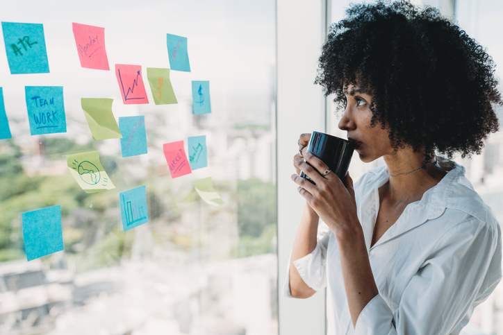 Pensive young adult businesswoman drinking coffee and looking at some adhesive notes on the big window