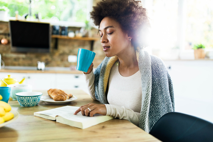 Black woman reading a book during morning coffee at home.
