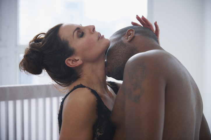 Man kissing neck of woman in bed