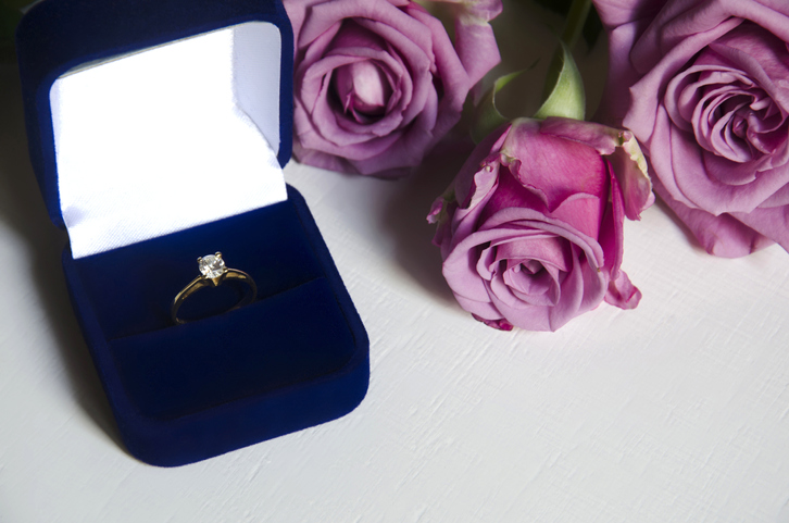 Engagement ring in a box and pink roses