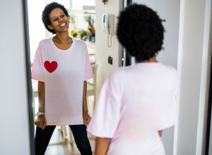 Happy young woman wearing t-shirt with heart shape looking in mirror