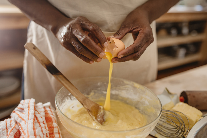 African American woman cracking eggs into a bowl of batter