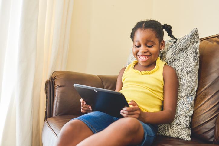 dark-skinned african-american girl watching tablet