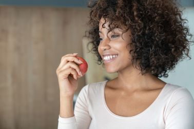 African American woman at home eating an apple