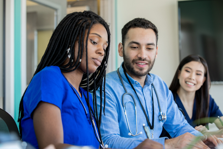 Group of medical professionals sitting at a conference table