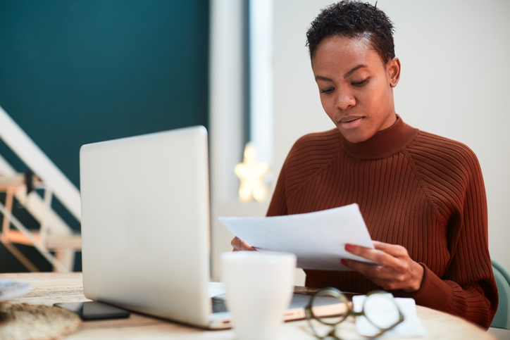 Woman working on her finances at home, filling up tax forms.