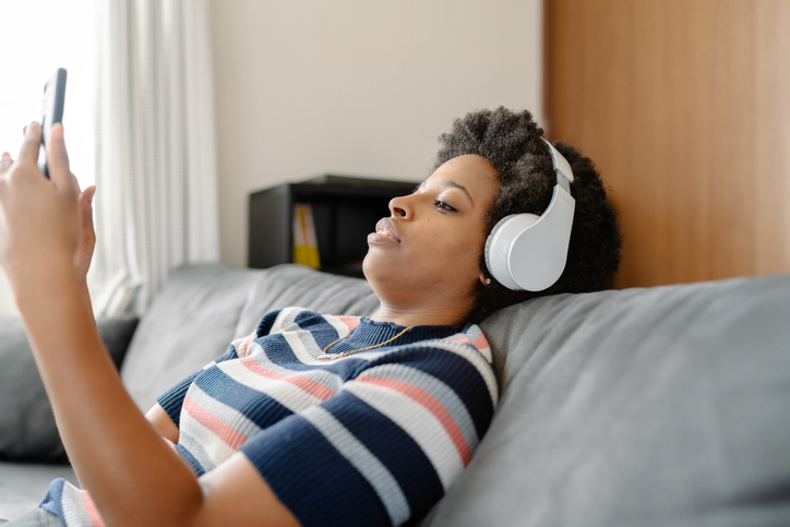 Young woman listening to music while sitting on sofa