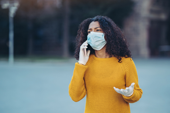 Worried young woman talking on the phone during flu epidemic