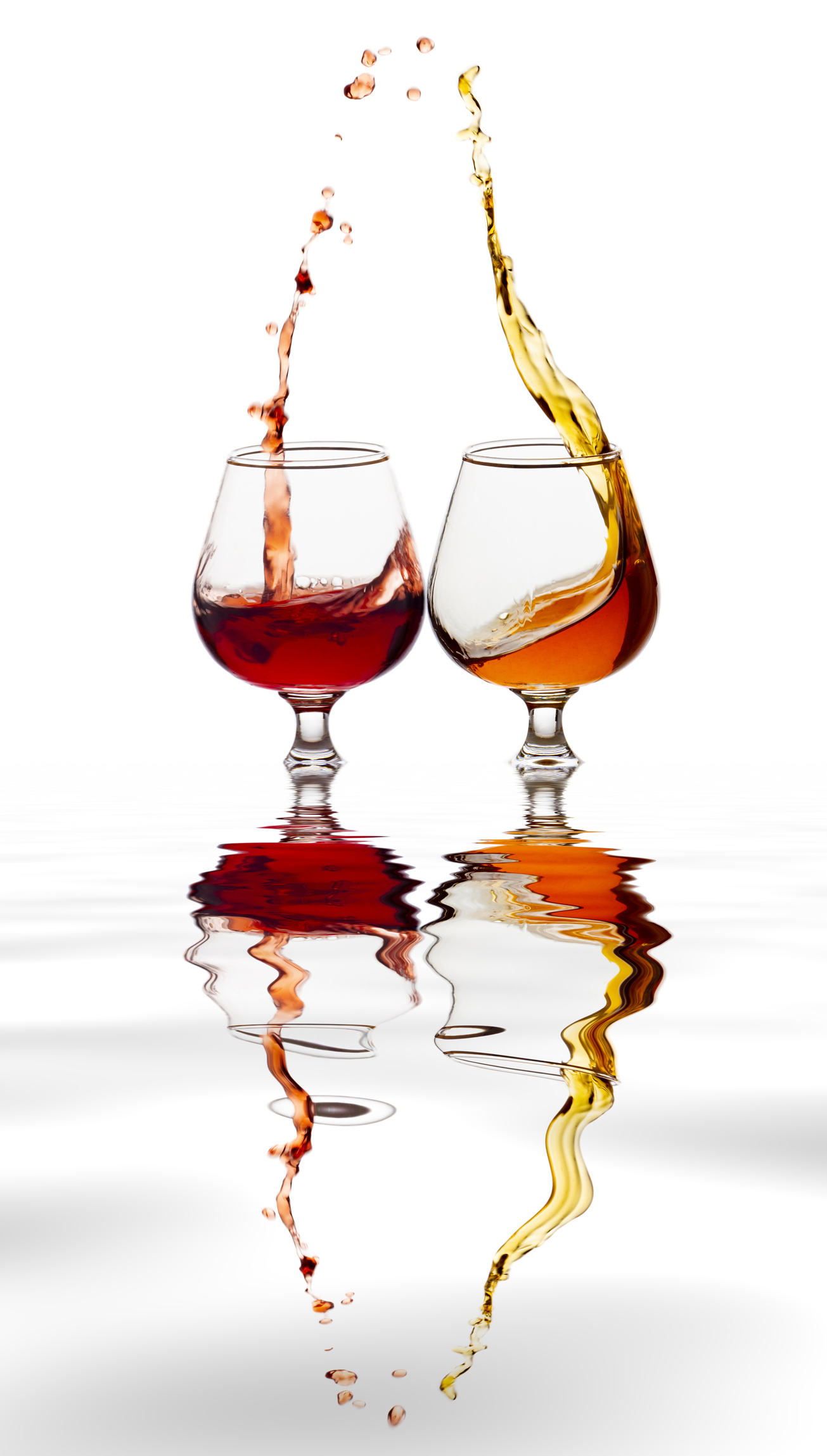 Raising a toast of liquor glasses on a white background reflected on a water surface.