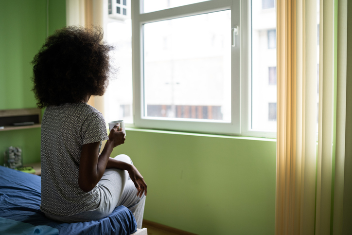 Sad afro woman sitting on a bed and drinking coffee