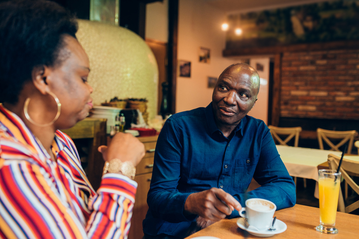 Mature African - American couple enjoying coffee before ordering dinner