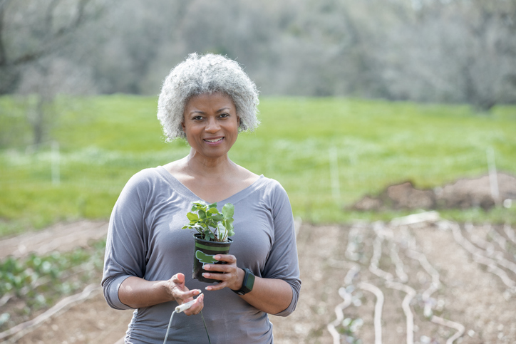 Senior woman smiles while holding plant in garden