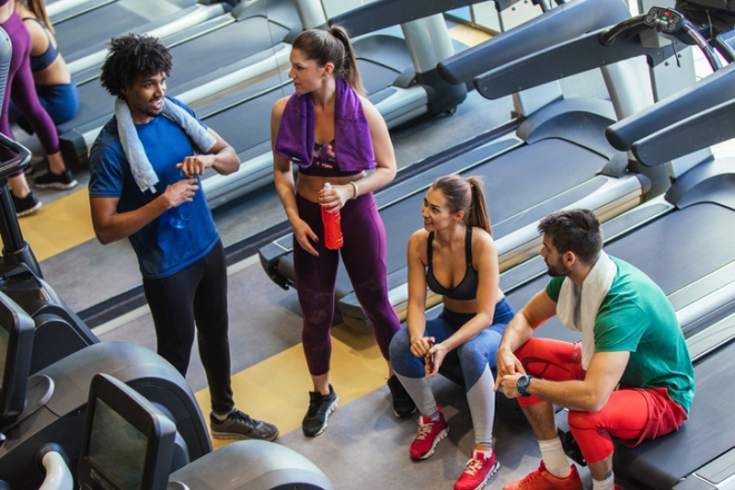 Young cheerful people resting from exercising at gym and communicating
