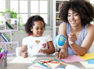 Mother and daughter using a globe at home