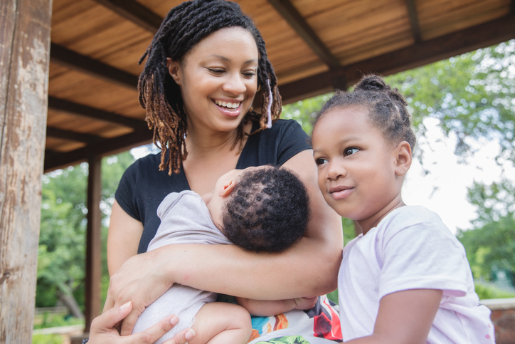 Mother smiles at toddler daughter while holding infant son