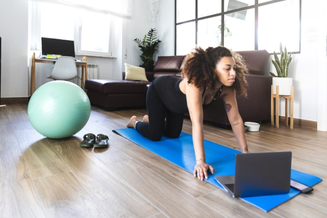 Pregnant woman practicing Yoga with online video class