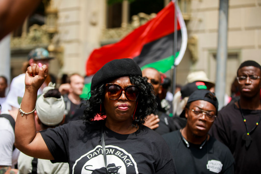 A member of the New Black Panthers makes a Black Power fist...