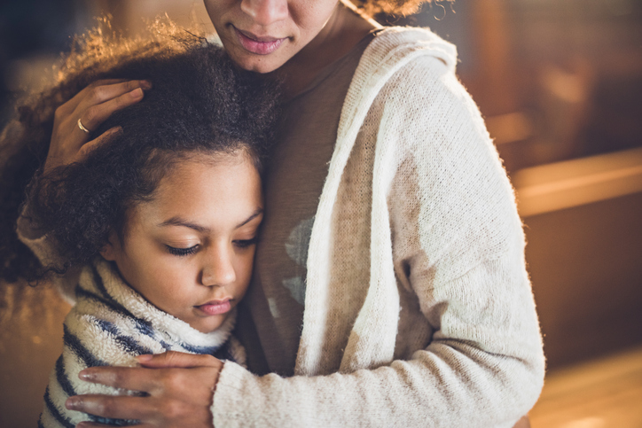 Sad African American girl embracing her mother at home.