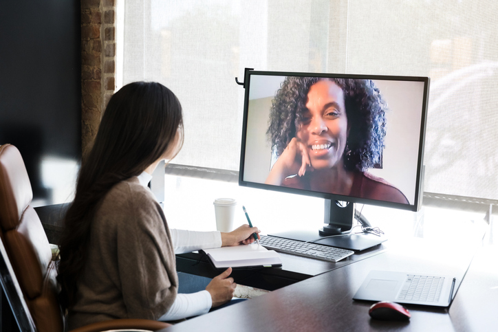 Businesswoman talks with female colleague online