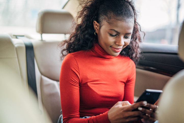 Black woman sitting in a back seat of a car and using on the smart phone