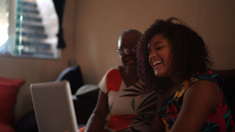 Grandmother and granddaughter having a video call on digital tablet at home