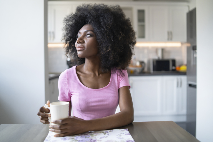 African woman drinking coffee home alone