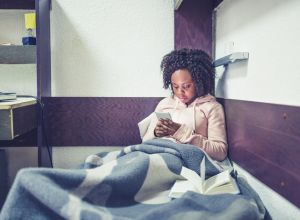 Young African female student , relaxing and listening music in a University campus room