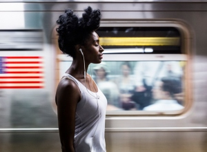 USA, New York City, Manhattan, woman with earphones on subway station platform