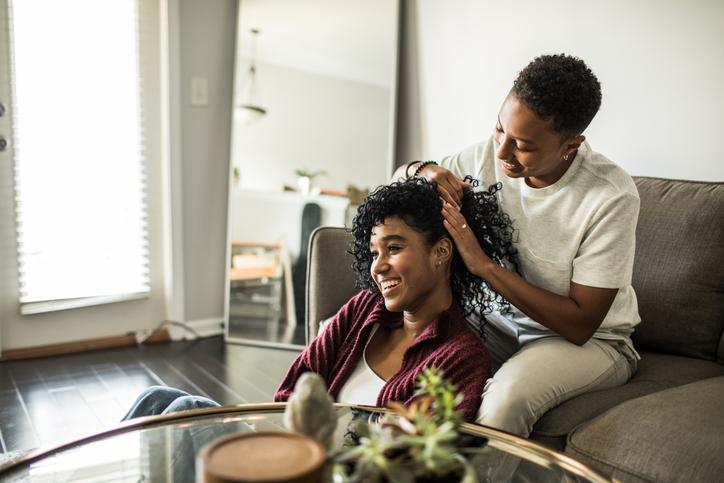 Woman brushing girlfriend's hair on couch