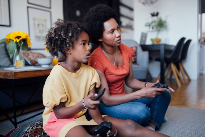 Side view of an African American mother and daughter playing video games together at home