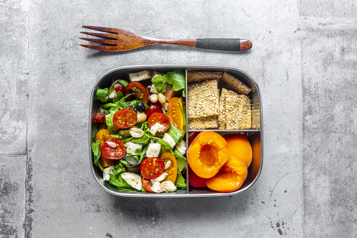 Lunch box with rocket salad with colored tomatoes, mozzarella and nuts, crispbread and apricots, wooden fork on concrete surface