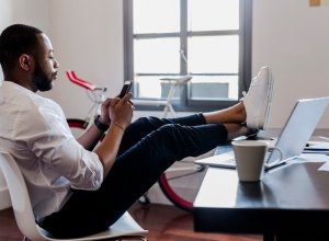 Man using cell phone in home office with feet on desk