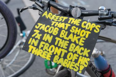 A placard calling for an arrest of the cops who shot Jacob...