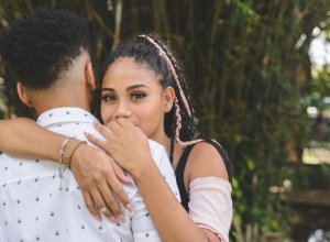 Portrait of young afro couple hugging in a public park. Rear view of the man. Woman looking at camera over the her boyfriend's shoulder.