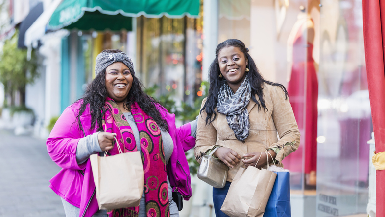 Two African-American women shopping in city