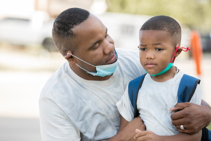 Father consoles anxious kindergartener while they wear masks as he's dropping him off for first day of school,