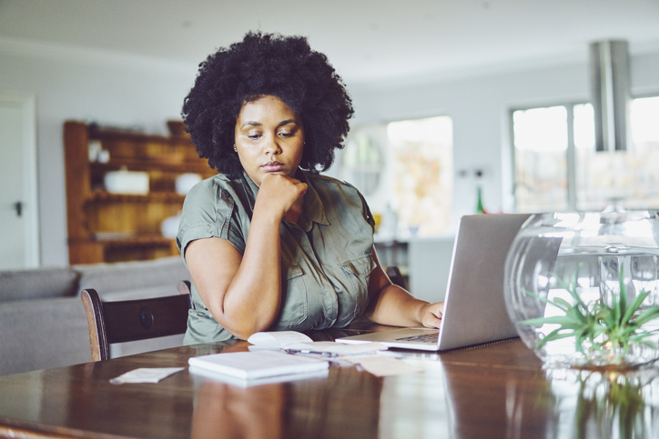 Woman looking concerned while paying bills from home