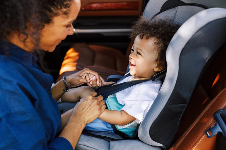 Smiling Boy Looking At Mother Tying Seat Belt