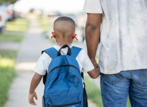Father holding elementary age sons hand while walking to school