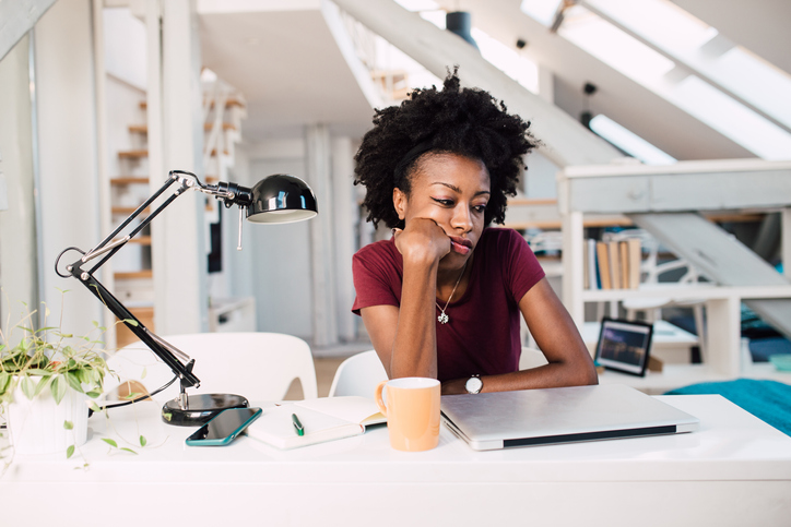 African-American woman sitting at her home office, bored of working