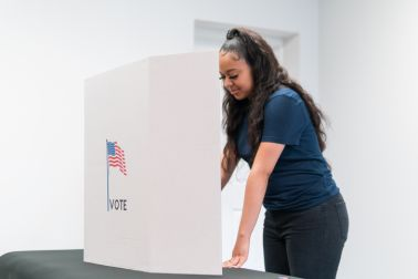 Young woman casts ballot at voting station