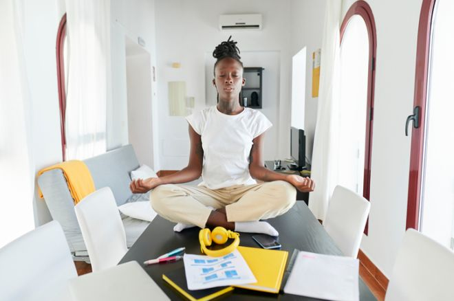 Businesswoman meditating while sitting by laptop and book on desk at home