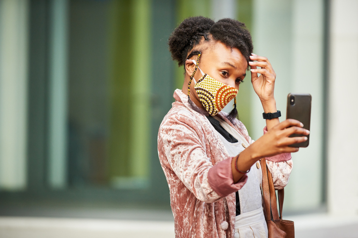 Young woman in a face mask taking selfies on a city street