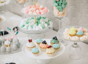 Multicolored Meringue, vanilla and chocolate cupcakes with cream frosting, decorated with fresh berries, close-up on a white glass dish, on a festive wedding table. The concept of food and confectionery. Buffet table with sweets.