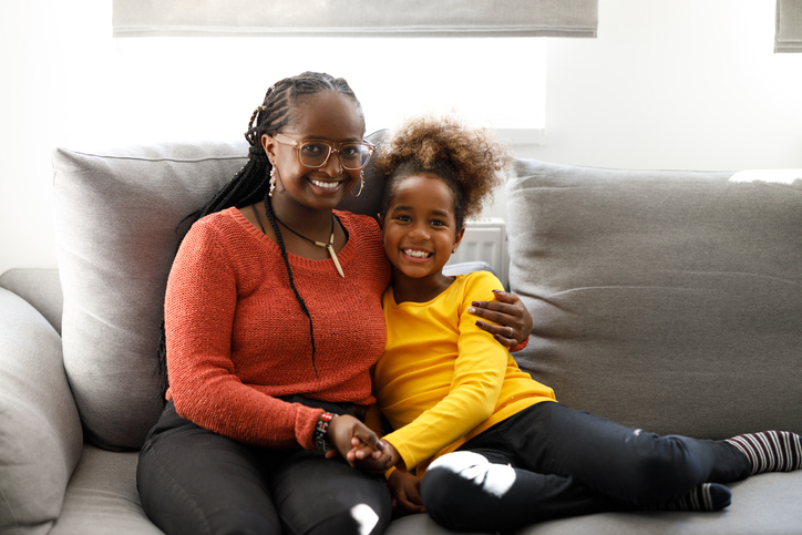 An African girl is hugging her mother on a Christmas day.